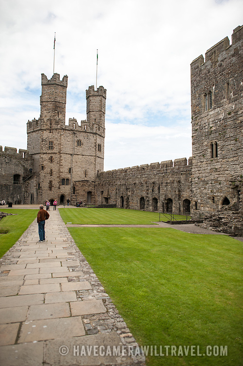 A path on the interior courtyard at Caernarfon Castle in northwest Wales. A castle originally stood on the site dating back to the late 11th century, but in the late 13th century King Edward I commissioned a new structure that stands to this day. It has distinctive towers and is one of the best preserved of the series of castles Edward I commissioned.