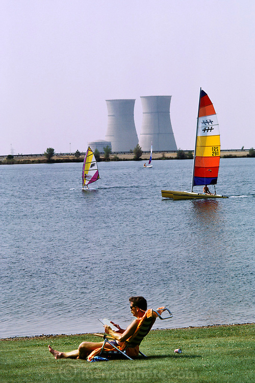 Nuclear Energy: Picnic area and windsurfers enjoy the cooling pond for the Nuclear Power Plant in Rancho Seco, California (1987). Cooling towers on opposite shore.