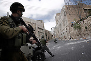 Israeli soldiers take position during clashes in  the West Bank city of Hebron February 12, 2010. Palestinians clashed with Israeli troops in Hebron amid outrage over Israel's plan to restore two flashpoint Jewish holy sites in the occupied territory.