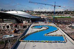 Olympic Park.  2 years to go. View of the F10 bridge with construction workers from the Aquatics Centre forming a giant number 2 to signify 2 years until the start of London 2012 Olympic Games.The Aquatics Centre and the Olympic Stadium are visible beyond.