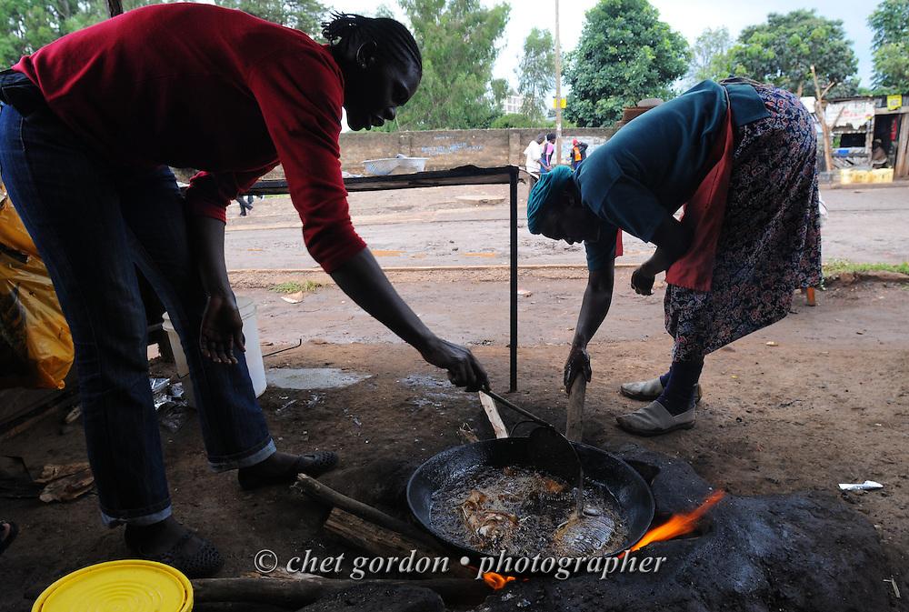 Two women fry tilapia fish pieces in the Kibera slum, Nairobi, Kenya on Tuesday, November 29, 2011. Kibera is one of Africa's largest slum with more than 200,000 inhabitants.