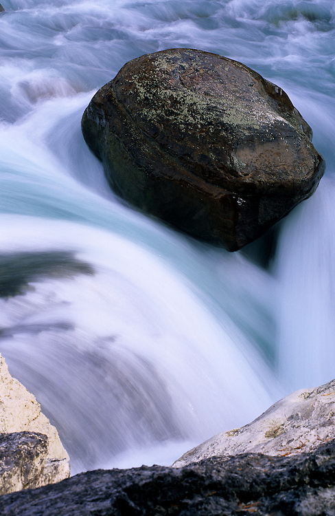 A huge rock stubbornly hangs on as the water of Sunwapta Falls flows its way around it