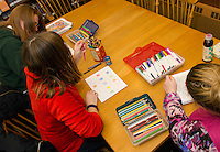 Jeannette Perez, Chelle Bergeron and Amy Winters chat and color during the Adult Coloring Hour at Hall Memorial Library in Northfield on Monday evening.  (Karen Bobotas/for the Laconia Daily Sun)