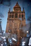Low angle view of Giralda Minaret, Seville Cathedral, Andalucia, Spain, pictured on December 24, 2006 reflected in a pond in the winter afternoon light. Seville Cathedral is the largest Gothic building in the world. It was converted from the original 12th century Almohad Mosque on this site during the 16th century and the original Moorish entrance court and Giralda Minaret are both integrated in the cathedral. Inside is the tomb of the explorer Christopher Columbus (1451-1506). The Giralda is constructed of cut bricks, originally 82 metres high, now 103 metres high with the 16th century belfry added to the original tower. Picture by Manuel Cohen