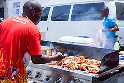 "Eustac Weekes grills stuffed lobster on the grill.  ""Alvin's Cultural Workshop"" Cultural Fair honoring Mr. Alvin Turnbull.  Emancipation Garden.  St. Thomas, VI.  29 April 2015.  © Aisha-Zakiya Boyd"