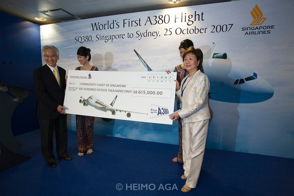 Airbus A380 first commercial flight - Singapore Airlines SQ 380 Singapore-Sydney on October 25, 2007. First flight send-off party at gatehold room F31, Changi Airport. Singapore Airlines Chairman Chew Choon Seng (yellow tie) presenting a S$ 615.000 cheque from the ebay auction of the first flight seats to Community Chest of Singapore.