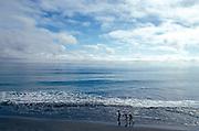 three figures walking along beach