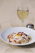 plate of linguine with bacon and fried egg and glass of white wine