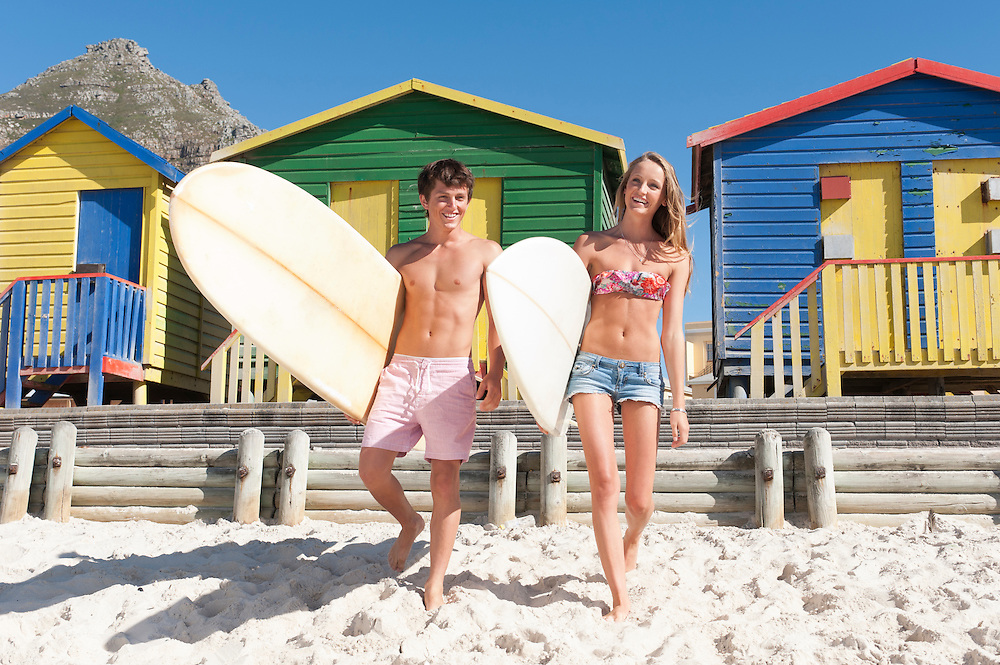Surfers on sandy beach with colourful beach hits in background