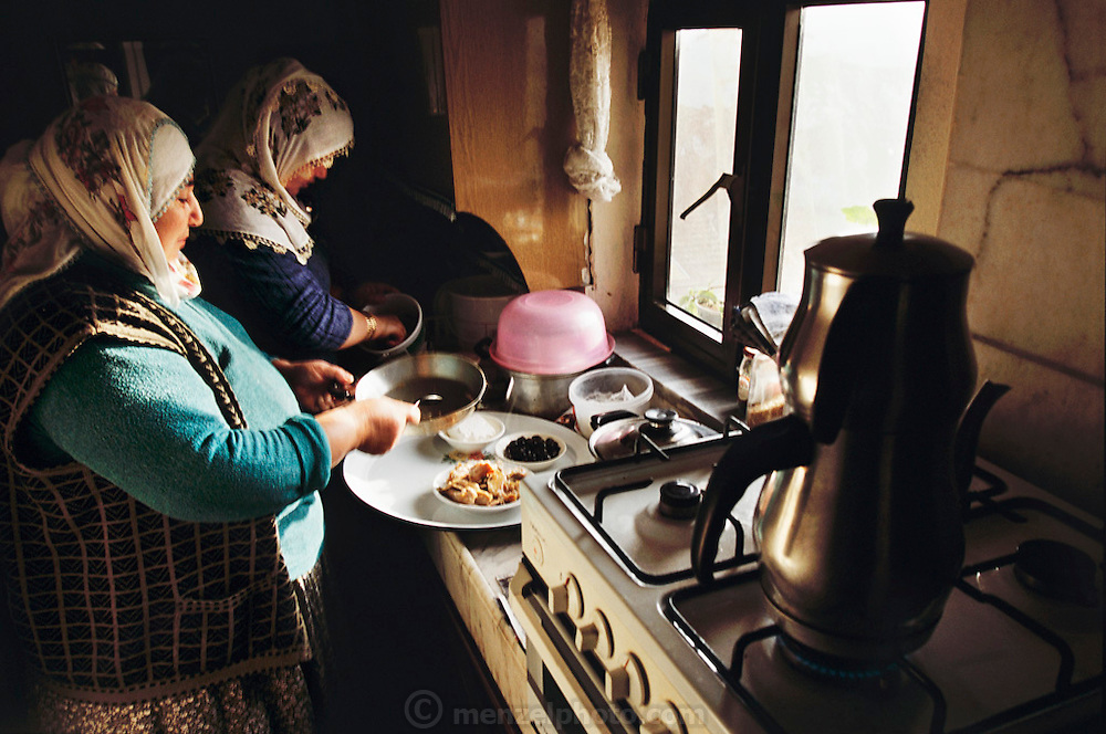 Safiye Çinar and her daughter-in-law Feriye prepare breakfast for their families in Feriye's downstairs apartment in the house they share in the Golden Horn (or Haliç) area of Istanbul, Turkey. They will serve tea, tomatoes, spiced meat, bread, feta cheese, olives, sugar, butter, and rose jam on a communal platter.