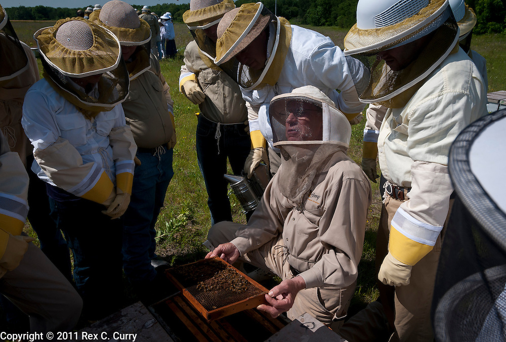 John Talbert shows students in his beekeeping class a frame of honey bees at his Sabine Creek Honey Farm in Royce City on May 7, 2011...