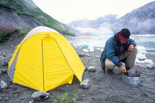 Glacier Bay National Park, Daniel J. Cox cooking dinner near McBride Glacier after day of kayaking. Alaska.