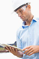 Male architect looking at tablet PC against sky