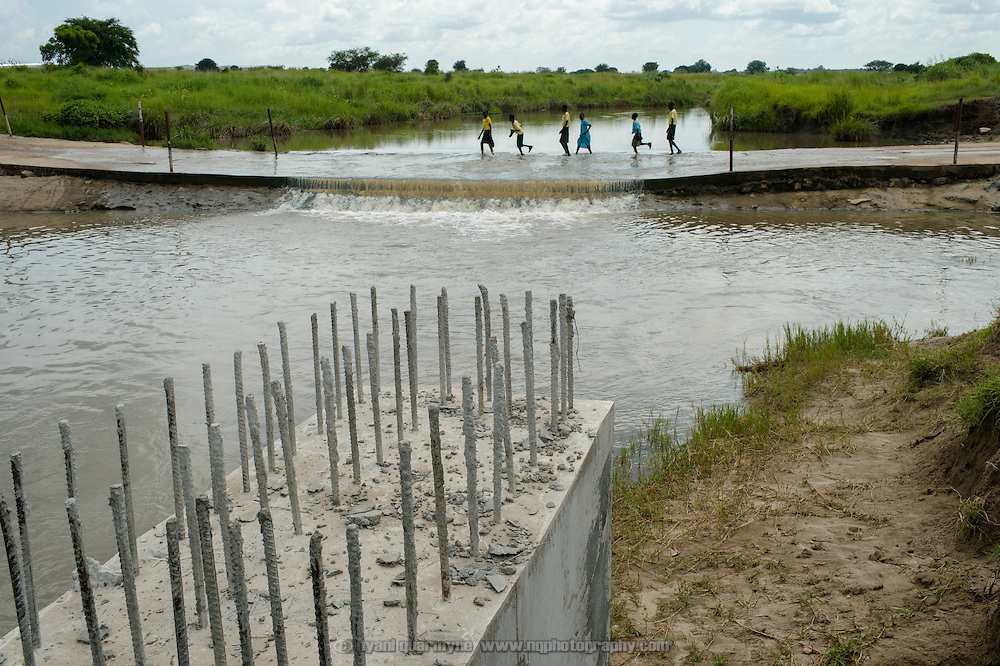 Plan International is constructing a bridge near Juba, South Sudan to anable school children to get to and from school when floods occur. In this image, children can be seen on the original roadway, some choosing to remove only one shoe and hop across the river. At times when the waters rise higher, they are unable to cross at all.
