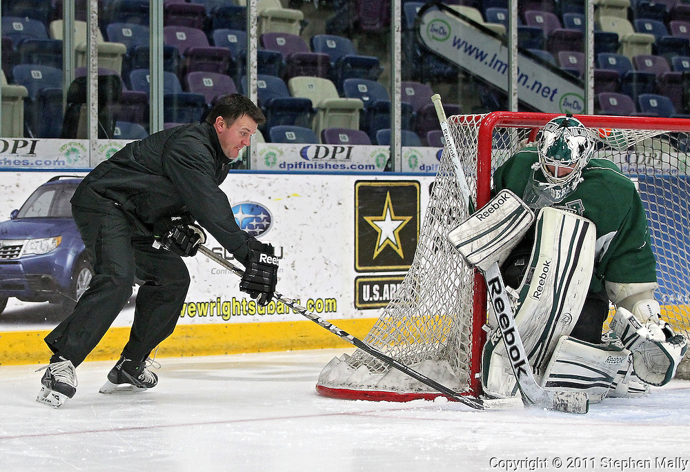 Goaltending coach Scott Meyer (from left) tries to score a goal on RoughRiders goalie Matt McNeely during a practice at the Cedar Rapids Ice Arena, 1100 Rockford Road SW, in Cedar Rapids on Tuesday, December 13, 2011. (Stephen Mally/Freelance)