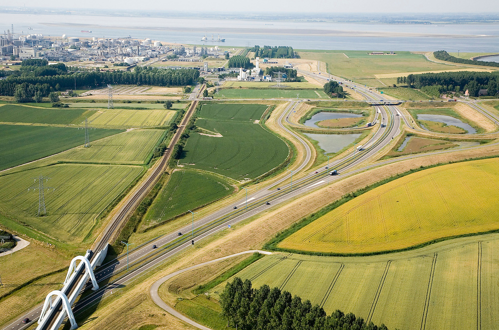 Nederland, Zeeland, Terneuzen, 04-07-2006;  het verkeersplein aan de Herbert Dowweg, ten westen van Terneuzen, is onderdeevan de toerit tot de Westerscheldetunneen geeft aansluiting op het landelijk wegennet; links de chemische industrie van Dow Chemical, boven de Schelde met in het verschiet Zuid-Beveland; Zeeuws-Vlaanderen, Zeeuwsch-Vlaanderen, planologie, verkeer en vervoer, tol, privaat publieke samenwerking, PPS, mobiliteit, auto, infrastructuur, milieu; zie ook andere (lucht)foto's van deze lokatie, deevan de serie Panorama Nederland<br />  luchtfoto (toeslag); aerial photo (additional fee required); .foto Siebe Swart / photo Siebe Swart