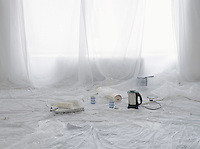 Empty room covered in dust sheets with kettle and painting supplies