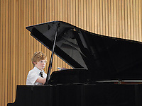 Pre teen boy playing piano in music class