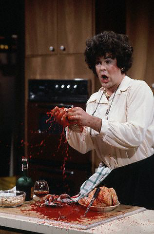 ca. 1977-1979, New York, New York, USA --- Dan Aykroyd in a  skit plays Julia Child cutting herself during a cooking show and bleeding to death. --- Image by © Owen Franken/CORBIS