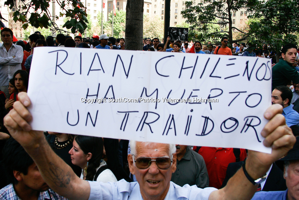 A man holds a banner that reads &quot;Chileans laugh a traitor has died&quot;.<br /> People also celebrated as the ruthless dictator died.<br /> December 2006, The Chilean Dictator Augusto Pinochet died in Santiago Chile. As news spread thousands went out the streets either to celebrate o mourn Pinochet who lead the 1973 coup that overthrew the democratically elected president Salvador Allende. Pinochet's 17 year regime killed and disappeared around 4.000 people, tortured and exile around 20.000. On 1989 he lost elections and democracy was regained. He died on late December 2006. December 2006, The Chilean Dictator Augusto Pinochet died in Santiago Chile. As news spread thousands went out the streets either to celebrate o mourn Pinochet who lead the 1973 coup that overthrew the democratically elected president Salvador Allende. Pinochet's 17 year December 2006, The Chilean Dictator Augusto Pinochet died in Santiago Chile. As news spread thousands went out the streets either to celebrate o mourn Pinochet who lead the 1973 coup that overthrew the democratically elected president Salvador Allende. Pinochet's 17 year.