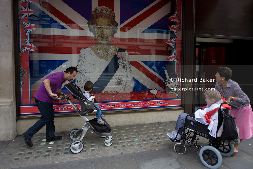 A father and child in a buggy and a daughter with her aged mother in a wheelchair admire a Lego representation of Queen Elizabeth ahead of a weekend of nationwide celebrations for the monarch's Diamond Jubilee. A few months before the Olympics come to London, a multi-cultural UK is gearing up for a weekend and summer of pomp and patriotic fervour as their monarch celebrates 60 years on the throne and across Britain, flags and Union Jack bunting adorn towns and villages.