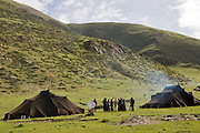 A group of Tibetan nomads show off their satellite dish outside the handmade yak-wool tents where they make their home in spring and summer in the Tibetan Plateau. The satellite dish was provided by China's central government; along with a solar battery charger, a truck battery, and a TV so the nomads can watch Chinese broadcasts and learn the Chinese language; an attempt, some say, to assimilate indigenous Tibetans.