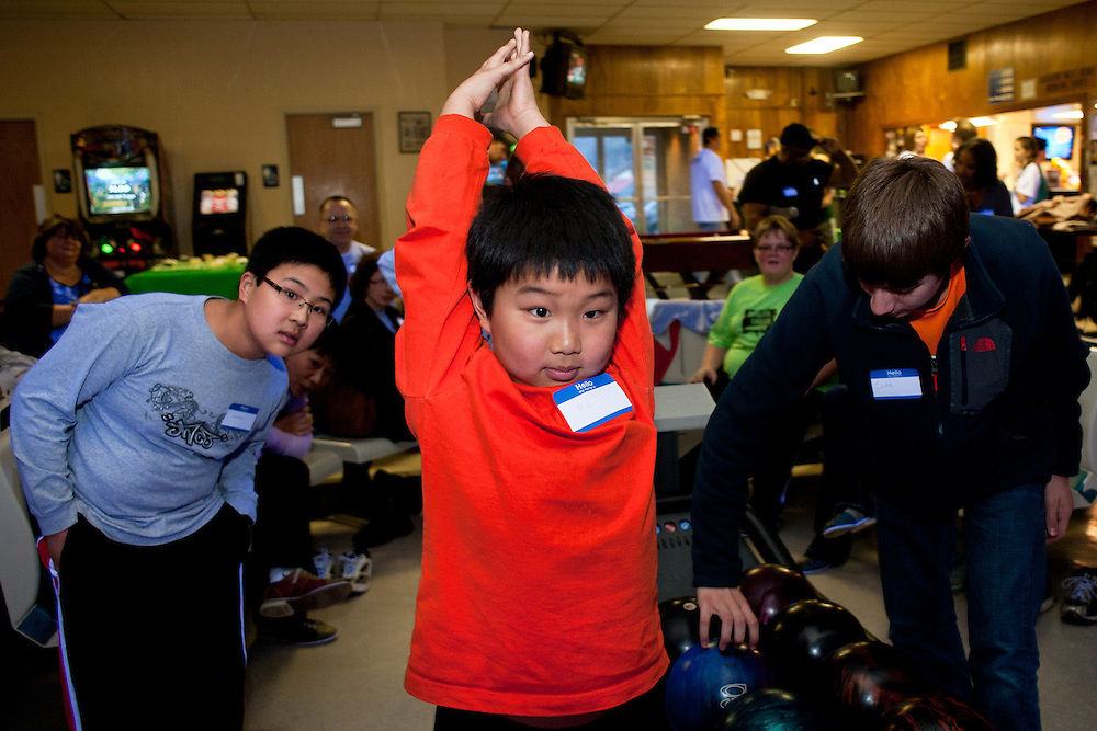 Eric Bi (center) and Alexander Bi (left) watch in anticipation as Eric Bi's ball hits the pins during the bowling party held for Contestants in the Scripps Spelling Bee. Photo by: Ross Brinkerhoff.