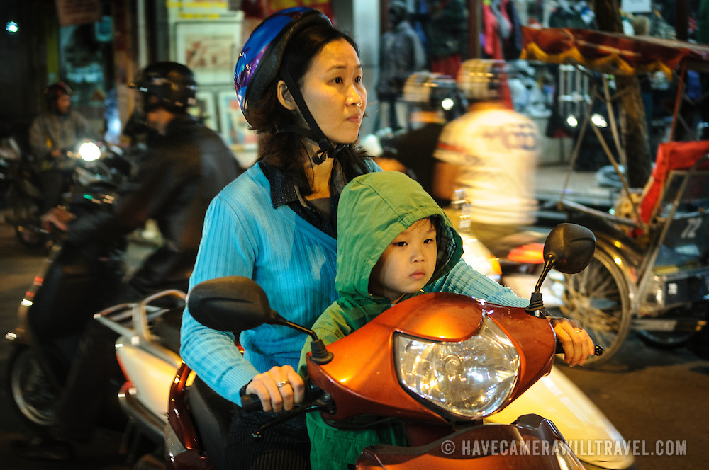 A mother and daughter ride a scooter on a busy street in downtown Hanoi's Old Quarter.