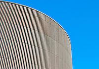Corrugated round building against a blue sky at Werdhölzli Sewage Treatment Plant, Zürich, Switzerland.