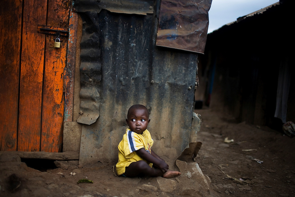 A young child sits alone in Mathare, one of the poorest slums in Nairobi.  Running water and electricity are scarce and trash and human waste fills the streets.  Many people have no jobs and those who do work can earn less than one dollar a day.