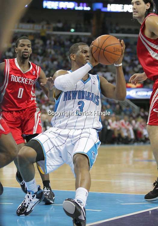 16 March 2009: New Orleans Hornets guard Chris Paul (3) passes the ball between Houston Rockets defenders Aaron Brooks (0) and Luis Scola (4) during a  95-84 loss by the New Orleans Hornets to the Houston Rockets at the New Orleans Arena in New Orleans, Louisiana.