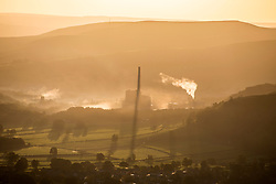 © Licensed to London News Pictures. 17/10/2019. Castleton UK. The sun rises this morning behind the Breedon Hope Cement Works in Castleton at the western end of the Hope Valley, Derbyshire. Photo credit: Andrew McCaren/LNP