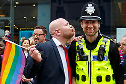 © Licensed to London News Pictures. 23/05/2015. Birmingham, UK. A LGBT campaigner kissing a police officer during The Birmingham Gay Pride Parade 2015 on New Street in Birmingham on Saturday 23 May 2015. Photo credit : Tolga Akmen/LNP