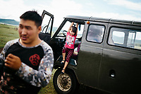 A young girl plays on a van in northern Mongolia.