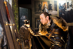 © Licensed to London News Pictures. 09/02/2015. London, UK. A man dressed as a character from the series takes a photograph of exhibits at the Game of Thrones Exhibition on 9th February 2014 at the O2 Arena in Greenwich, south-east London. Photo credit : Vickie Flores/LNP