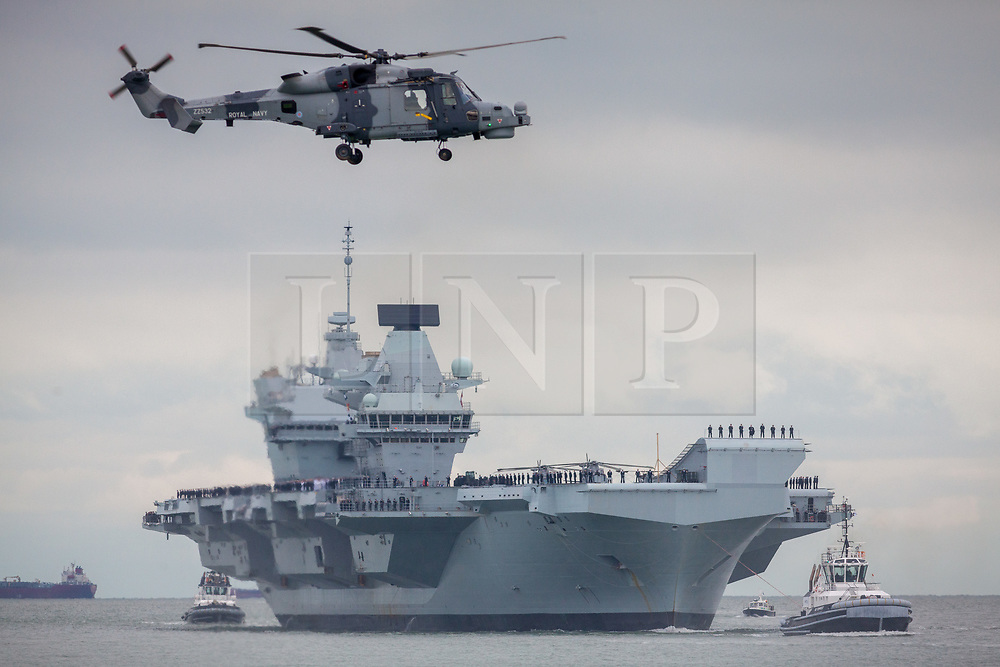 © Licensed to London News Pictures. 16/11/2019. Portsmouth, UK.  A Royal Navy Lynx hovers as HMS Prince of Wales, the Royal Navy's second Queen Elizabeth-class aircraft carrier, sails into Portsmouth Naval Base for the first time this afternoon, 16th November 2019. The £3.1 billion warship has been undergoing eight weeks of sea trials in the Moray Firth. Photo credit: Rob Arnold/LNP