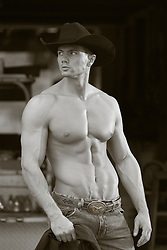 shirtless cowboy with a smooth muscular body by a barn