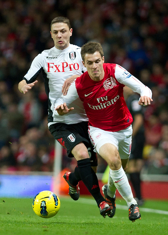 Arsenal's Aaron Ramsey fights for the ball with Fulham's Chris Baird during  their English Premier League  soccer match at the  Emirates stadium in London, Saturday, Nov. 26, 2011. (AP Photo/Bogdan Maran)