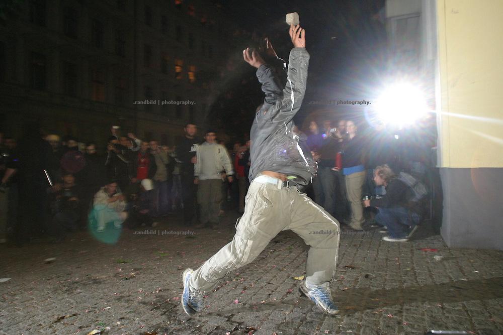 Während der 1.Mai Krawalle in Berlin wirft ein Demonstrant unter den Augen der Umstehenden und Medien einen Pflasterstein gegen die Polizei. A man throws during the 1.May riots a stone against the police