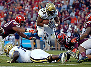Nov 12, 2016; Blacksburg, VA, USA;  Georgia Tech Yellow Jackets running back Marcus Marshall (34) jumps over offensive lineman Shamire Devine (71) against Virginia Tech Hokies defensive tackle Woody Baron (60) during the second quarter at Lane Stadium. Mandatory Credit: Peter Casey-USA TODAY Sports