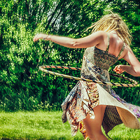 Young woman wearing a summer dress spinning a hoop standing outdoors