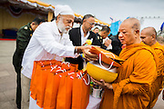 "22 JULY 2014 - BANGKOK, THAILAND: A Thai-Indian Sikh makes merit by presenting alms to Buddhist monks at Sanam Luang in Bangkok. Hundreds of Thai military officers and civil servants attended a Buddhist chanting service and merit making ceremony to mark the 2nd month anniversary of the May 22 coup that deposed the elected civilian government and ended nearly six months of sometimes violent anti-government protests. The ruling junta said the ceremonies Tuesday were the kickoff to a ""Festival to Bring Back Happiness of the People of the Nation."" There will be free concerts, historical pageants and movies at Sanam Luang, a large parade ground near the Ministry of Defense in Bangkok.    PHOTO BY JACK KURTZ"