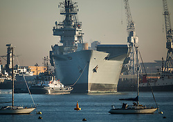 © Licensed to London News Pictures. 1/12/2016. Portsmouth, UK. Tugs move the former Royal Navy aircraft carrier HMS Illustrious from Portsmouth Naval Base out into the harbour ahead of her final voyage to a scrap yard.  Illustrious, the last of the Invincible Class carriers, has been sold to the Leyal Ship Recycling and Dismantling company in Aliaga, Turkey - the same yard that dismantled her sister ships Ark Royal and Invincible. Photo credit: Peter Macdiarmid/LNP
