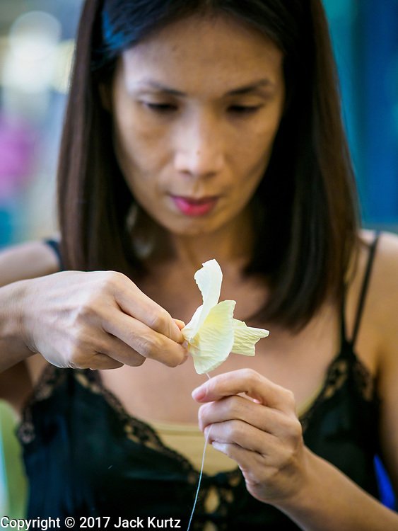 "24 MAY 2017 - BANGKOK, THAILAND: A woman at the Emporium, an upscale shopping mall in Bangkok, makes wooden roses to be used during the cremation of Bhumibol Adulyadej, the Late King of Thailand. In Thai culture it is customary to place wooden flowers in front of a deceased person's coffin or urn as a last tribute before cremation. The Royal Cremation Organisation Committee, which is overseeing plans for the cremation of Bhumibol Adulyadej, the Late King of Thailand, asked the Bangkok Metropolitan Administration (BMA) to provide three million wooden flowers for the late King's cremation. The BMA, in turn, has asked malls and civic organizations to provide flowers. The Mall Group, which owns Emporium, has pledged to provide up to one million wooden ""Wiangping"" roses, which in Thai culture symbolize unconditional love. The late King will be cremated October 26, 2017.     PHOTO BY JACK KURTZ"