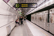 Train enters a metro station in Vienna, Austria Passengers are waiting on the platform