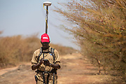 Moses Mawa is using a Differential Global Positioning System (DGPS) to accurately mark a stretch of cleared road between Pariang and Panakuach in Unity, on which UNMAS was tasked to conduct route clearance assessment. The legacy of conflict has resulted in most roads and other areas around Bentiu being contaminated with mines, such as anti-tank mines, and explosive remnants of war. Since 2013, there have been several vehicle mine accidents, which has meant some roads have been abandoned. UNMAS conducts survey and clearance for roads to ensure that civilians, humanitarians and the United Nations can safely use these roads.<br />