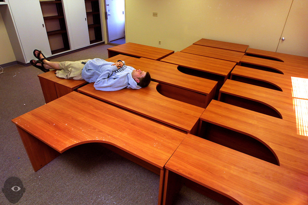 Cerulic employee Micah McNelly takes a break on desks once used in the offices of the Bluetooth wireless technology company. They are is ceasing operations after only 8 months and he and many others must now find new jobs.