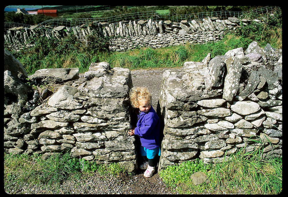 Little girl peeks between stone walls in cemetery at Kilmalkedar Church on the Dingle Peninsula; southwest Ireland.