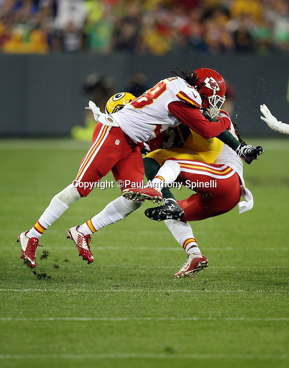 Green Bay Packers wide receiver Randall Cobb (18) gets gang tackled in the air by Kansas City Chiefs strong safety Ron Parker (38) and a teammate on a third quarter pass reception for a first down during the 2015 NFL week 3 regular season football game against the Kansas City Chiefs on Monday, Sept. 28, 2015 in Green Bay, Wis. The Packers won the game 38-28. (©Paul Anthony Spinelli)