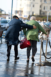 © Licensed to London News Pictures. 01/02/2014. Porthcawl, Wales, UK. Residents of Porthcawl  battle with heavy winds near the promenade after the seaside resort took a battering from huge waves early this morning. Photo credit : Graham M. Lawrence/LNP